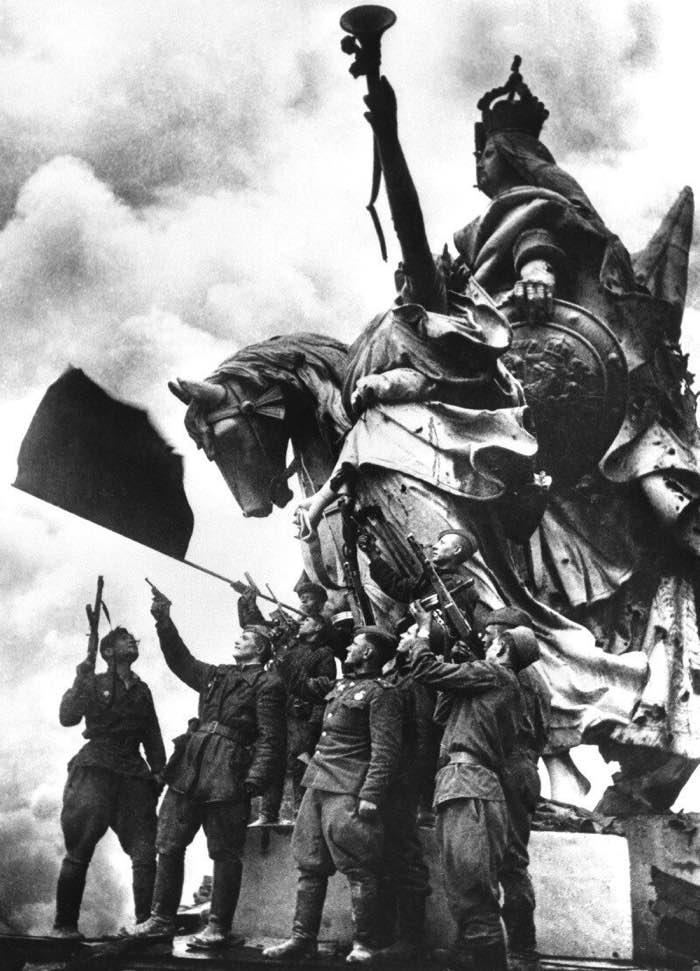 Бойцы подразделения капитана Неустроева салютуют знамени Победы, водруженному на крыше Рейхстага